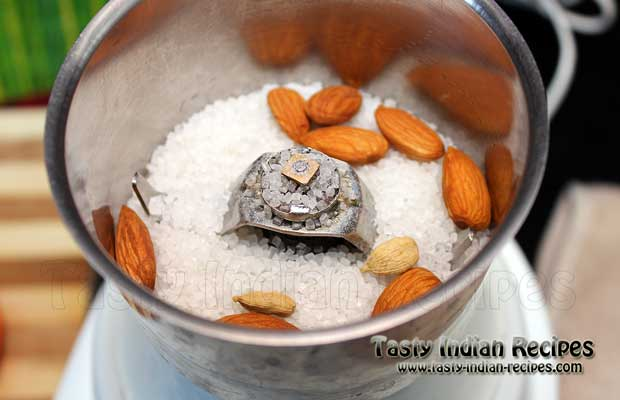 Put sugar, almonds and green cardamom in mixer grinder