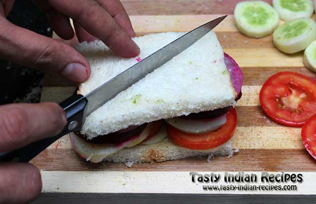 Cover the sandwich with another bread slice and press it lightly to cut into two pieces